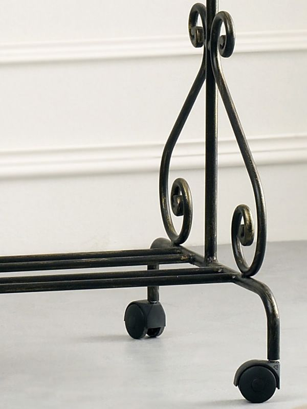 Detail of the dress rack in black varnished with antique golden effect