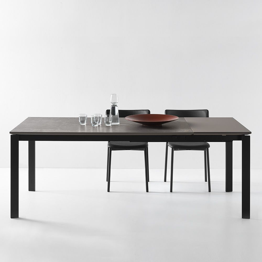 Extendable table made of black varnished metal with ceramic top