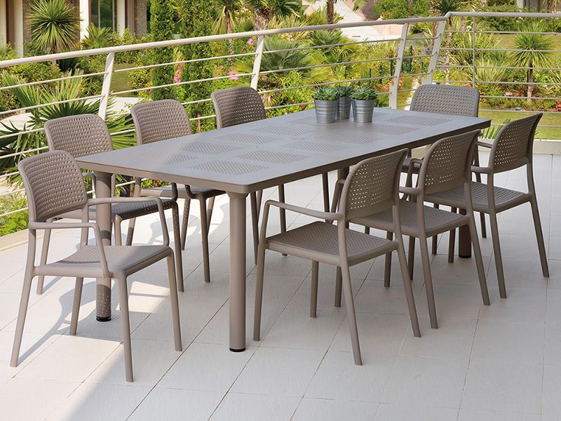 Extendable table (here open) made of dove resin, legs with round section, matching with Bora armchairs